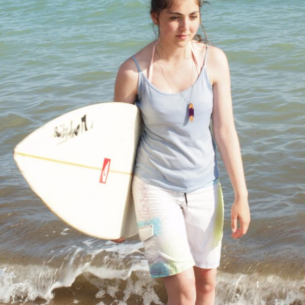 surfboard necklaces being modeled on the beach